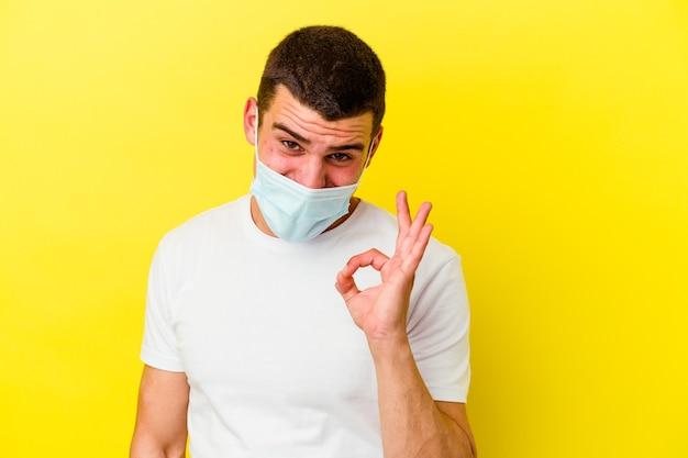 Młody kaukaski mężczyzna ubrany w ochronę przed koronawirusem na żółtej ścianie mruga okiem i trzyma w porządku gest ręką