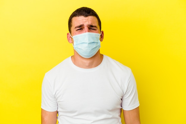 Młody kaukaski mężczyzna ubrany w ochronę przed koronawirusem na żółtej ścianie skomlący i płaczący niepocieszony