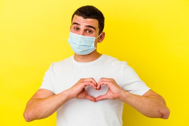 Młody kaukaski mężczyzna ubrany w ochronę przed koronawirusem na żółtej ścianie, uśmiechając się i pokazując kształt serca rękami.