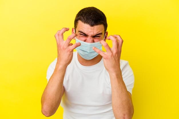 Młody kaukaski mężczyzna ubrany w ochronę przed koronawirusem na żółtej ścianie zdenerwowany krzyczący z napiętymi rękami.