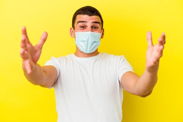 Młody kaukaski mężczyzna ubrany w ochronę przed koronawirusem na żółtym tle czuje się pewnie przytulając aparat.