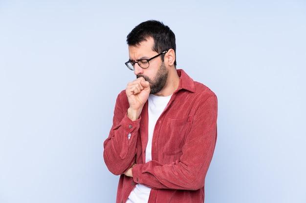 Młody kaukaski mężczyzna ubrany w sztruksową kurtkę na niebieskiej ścianie cierpi na kaszel i źle się czuje