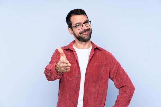 Młody kaukaski mężczyzna ubrany w sztruksową kurtkę na niebieskiej ścianie drżenie rąk do zamknięcia dobrą ofertę