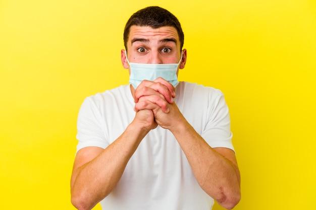 Młody kaukaski mężczyzna ubrany w żółtą ochronę przed koronawirusem modlący się o szczęście, zdumiony i otwierający usta, patrząc do przodu.