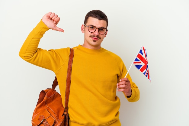 Młody kaukaski mężczyzna uczący się angielskiego na białej ścianie czuje się dumny i pewny siebie, przykład do naśladowania.