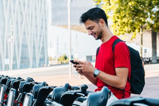 Młody kaukaski mężczyzna uśmiecha się i pisze na swoim telefonie komórkowym na zewnątrz