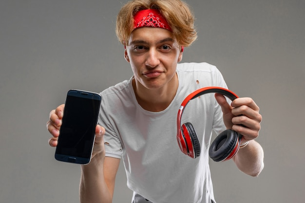 Młody kaukaski mężczyzna w czerwonych okularach przeciwsłonecznych, biała koszulka słucha muzyki z dużymi czerwonymi słuchawkami na szarej ścianie