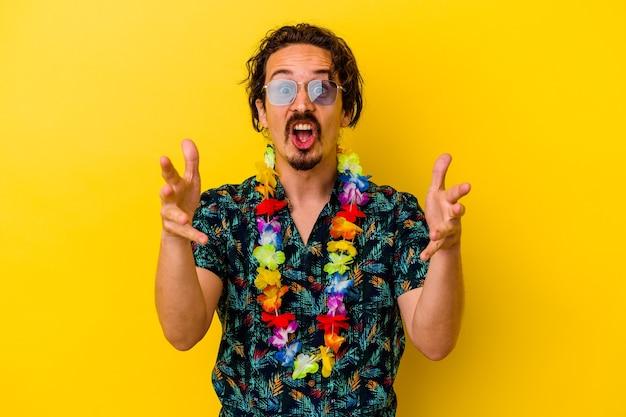 Młody kaukaski mężczyzna w hawajskim naszyjniku na żółtej ścianie otrzymujący miłą niespodziankę, podekscytowany i podnoszący ręce.