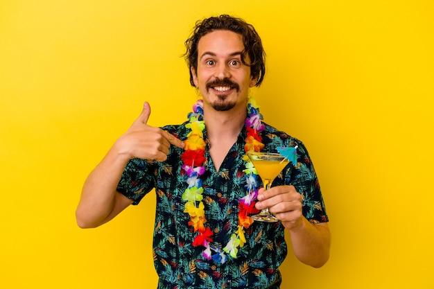 Młody kaukaski mężczyzna w hawajskim naszyjniku trzymający koktajl na żółtej ścianie osoba wskazująca ręką na miejsce na kopię koszuli, dumny i pewny siebie