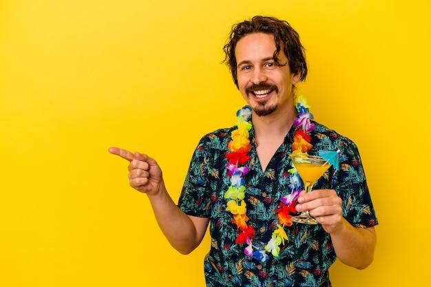 Młody kaukaski mężczyzna w hawajskim naszyjniku trzymający koktajl na żółtej ścianie, uśmiechnięty i wskazujący na bok, pokazujący coś w pustej przestrzeni