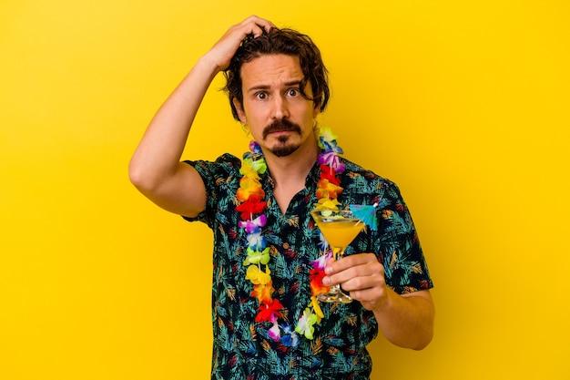 Młody kaukaski mężczyzna w hawajskim naszyjniku trzymający koktajl na żółtym tle, będąc w szoku, przypomniał sobie ważne spotkanie.