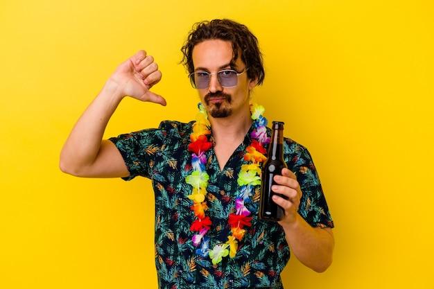 Młody kaukaski mężczyzna w hawajskim naszyjniku trzymający piwo na żółtym tle czuje się dumny i pewny siebie, przykład do naśladowania.