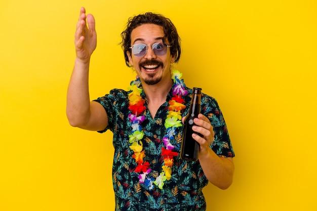 Młody kaukaski mężczyzna w hawajskim naszyjniku trzymający piwo odizolowane na żółto, otrzymując miłą niespodziankę, podekscytowany i podnoszący ręce.