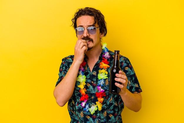 Młody kaukaski mężczyzna w hawajskim naszyjniku trzymający piwo odizolowane na żółtych obgryzających paznokciach, nerwowy i bardzo niespokojny.