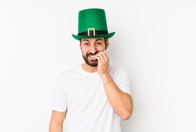 Młody kaukaski mężczyzna w kapeluszu świętego patryka na białym tle obgryzając paznokcie, nerwowy i bardzo niespokojny.