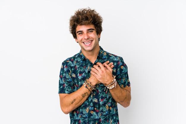 Młody kaukaski mężczyzna w koszulce z kwiatkiem na białym tle ma przyjazny wyraz, naciskając dłoń na klatkę piersiową. koncepcja miłości.