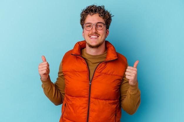 Młody kaukaski mężczyzna w okularach na białym tle na niebieskiej ścianie, podnosząc oba kciuki do góry, uśmiechnięty i pewny siebie