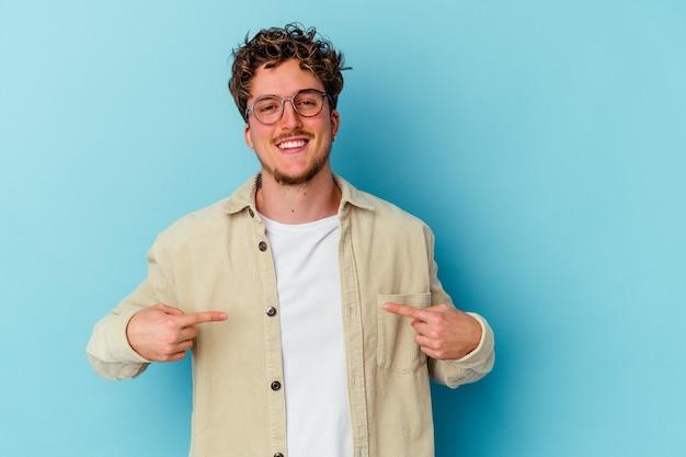 Młody kaukaski mężczyzna w okularach na niebieskiej osobie, wskazując ręką na przestrzeni kopii koszuli, dumny i pewny siebie