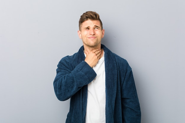 Młody kaukaski mężczyzna w piżamie cierpi ból gardła z powodu wirusa lub infekcji.