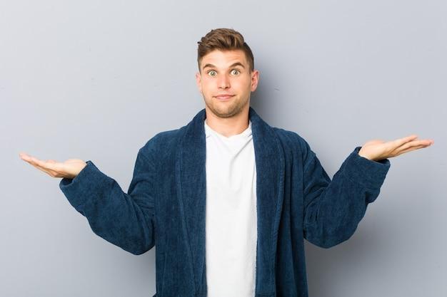 Młody kaukaski mężczyzna w piżamie sprawia, że skaluje się z rękami, czuje się szczęśliwy i pewny siebie.