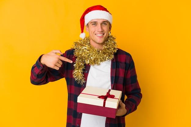 Młody kaukaski mężczyzna w świątecznym kapeluszu trzymający prezent na żółtych, gryzących paznokciach, nerwowy i bardzo niespokojny.