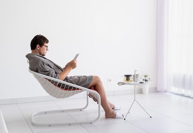 Młody kaukaski mężczyzna w szarych szlafrokach siedzi w salonie, relaksując się i pijąc zieloną herbatę, używając tabletu