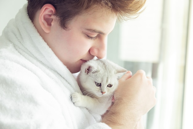 Młody kaukaski mężczyzna w szlafroku trzyma białą kotkę. stoi w pobliżu okna wczesnym rankiem.