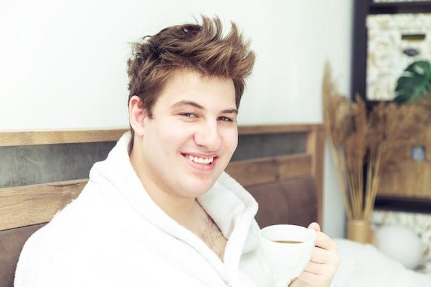 Młody kaukaski mężczyzna w szlafroku z filiżanką kawy, patrząc i uśmiechnięty. wcześnie rano w łóżku.