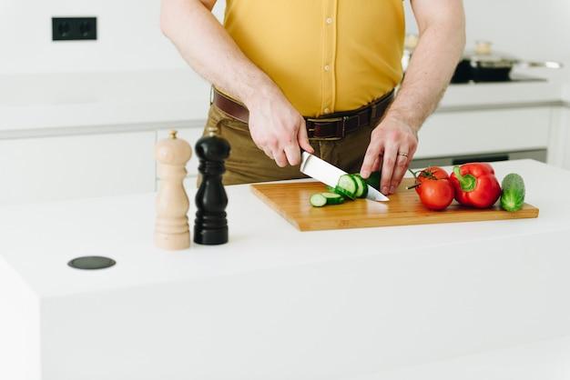 Młody kaukaski mężczyzna w żółtej koszulce gotuje zdrowy jarzynowy posiłek lub sałatki w białej nowożytnej kuchni z nożowy ono uśmiecha się