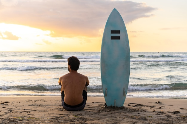 Młody kaukaski mężczyzna wstaje wcześnie, aby surfować o wschodzie słońca