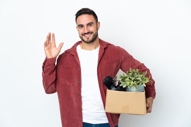Młody kaukaski mężczyzna wykonuje ruch podczas podnoszenia pudełka pełnego rzeczy na białym tle, pozdrawiając ręką z szczęśliwym wyrazem twarzy