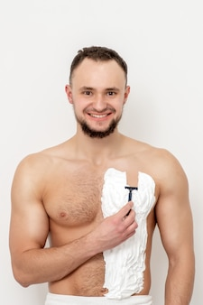 Młody kaukaski mężczyzna z brodą trzyma brzytwę goli klatkę piersiową białą pianką do golenia na białej ścianie. mężczyzna goli tułów