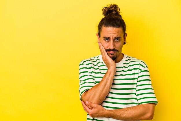 Młody kaukaski mężczyzna z długimi włosami na białym tle na żółtym tle, który czuje się smutny i zamyślony, patrząc na miejsce.