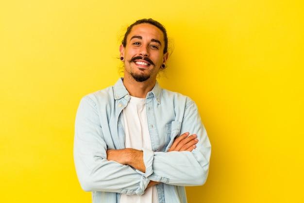 Młody kaukaski mężczyzna z długimi włosami na białym tle na żółtym tle śmiechu i zabawy.