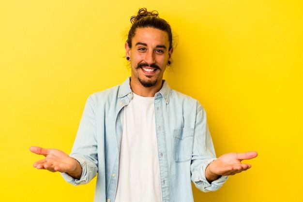 Młody kaukaski mężczyzna z długimi włosami na białym tle na żółtym tle sprawia, że łuska rękoma, czuje się szczęśliwy i pewny siebie.
