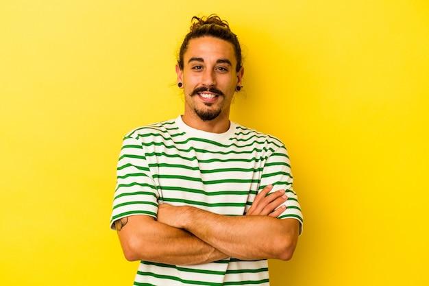 Młody kaukaski mężczyzna z długimi włosami na białym tle na żółtym tle szczęśliwy, uśmiechnięty i wesoły.