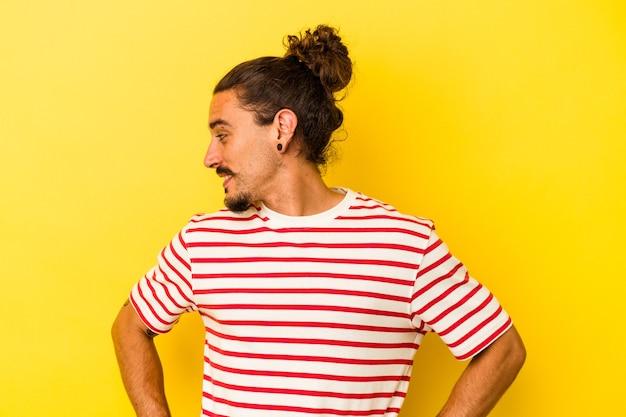 Młody kaukaski mężczyzna z długimi włosami na żółtym tle śmieje się radośnie i bawi się trzymając ręce na brzuchu.