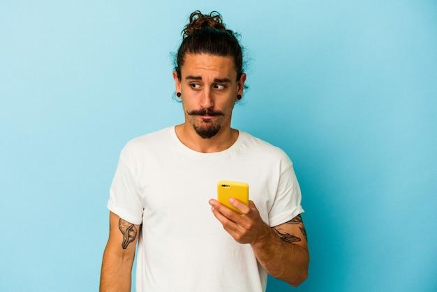 Młody kaukaski mężczyzna z długimi włosami trzymający telefon komórkowy na białym tle na niebieskim tle zdezorientowany, czuje się wątpliwy i niepewny.