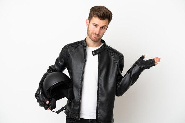 Młody kaukaski mężczyzna z kaskiem motocyklowym na białym tle mający wątpliwości podczas podnoszenia rąk