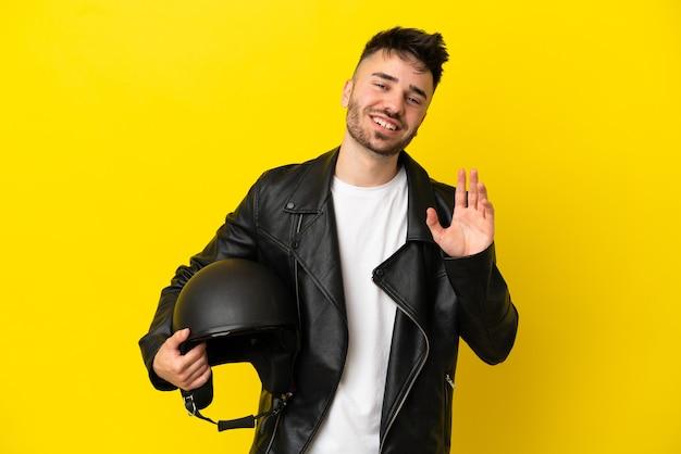 Młody kaukaski mężczyzna z kaskiem motocyklowym na białym tle na żółtym tle pozdrawiający ręką ze szczęśliwym wyrazem twarzy