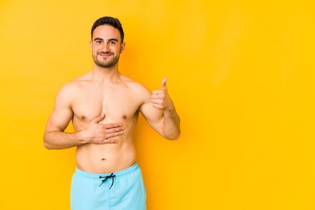 Młody kaukaski mężczyzna z kostiumem kąpielowym na białym tle na żółtej ścianie młody kaukaski mężczyzna z trtouches brzuch, uśmiecha się delikatnie, koncepcja jedzenia i satysfakcji.