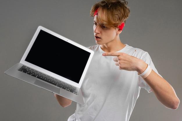 Młody kaukaski mężczyzna z krótkimi czerwonymi kręconymi włosami w białej koszulce, czerwonych okularach na szarym tle pokazuje laptopa i jest zaskoczony