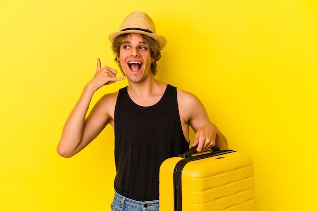 Młody kaukaski mężczyzna z makijażem będzie podróżować na białym tle na żółtym tle pokazując gest połączenia z telefonem komórkowym palcami.