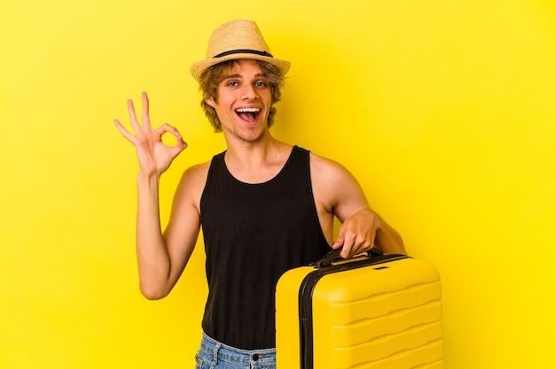 Młody kaukaski mężczyzna z makijażem będzie podróżować na białym tle na żółtym tle wesoły i pewny siebie pokazując ok gest.