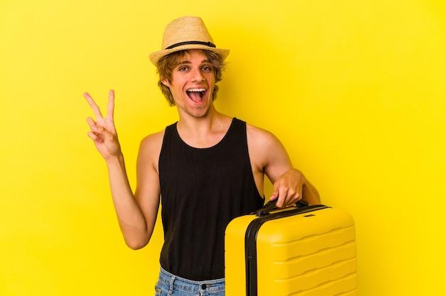 Młody Kaukaski Mężczyzna Z Makijażem Będzie Podróżować Na Białym Tle Na żółtym Tle Wyświetlono Numer Dwa Palcami. Premium Zdjęcia