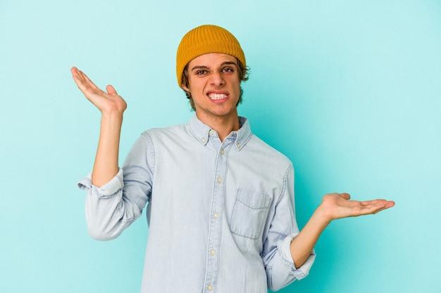 Młody kaukaski mężczyzna z makijażem na białym tle na niebieskim tle mylić i wątpliwe wzruszając ramionami, aby trzymać miejsce na kopię.