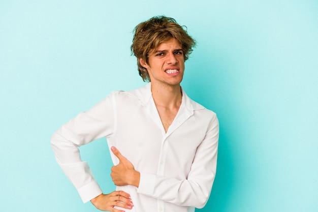 Młody kaukaski mężczyzna z makijażem na białym tle na niebieskim tle o ból wątroby, ból brzucha.