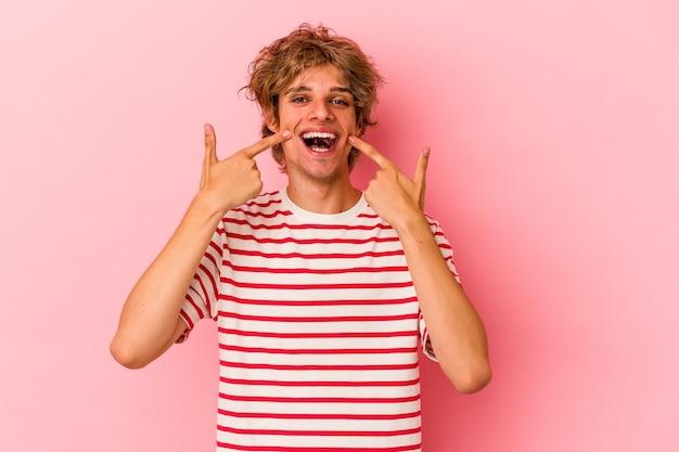 Młody kaukaski mężczyzna z makijażem na białym tle na różowym tle uśmiecha się, wskazując palcami na usta.