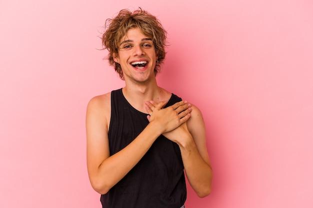 Młody kaukaski mężczyzna z makijażem na różowym tle ma przyjazny wyraz, przyciskając dłoń do klatki piersiowej. koncepcja miłości.