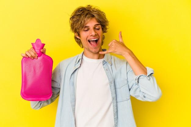 Młody kaukaski mężczyzna z makijażem trzyma gorącą torbę wody na białym tle na żółtym tle pokazując gest połączenia z telefonu komórkowego palcami.